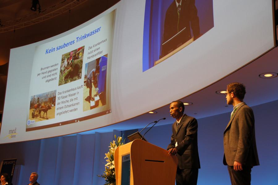 Dr. Elson Randrianantenaina und Dr. Julius Emmrich sprechen im Plenum beim Praxis Update 2013 in Berlin.